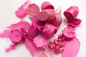 Pink lipstick chopped closeup on white background. Cosmetics commercial, beautiful style. Expensive smear, creative advertising, beauty concept