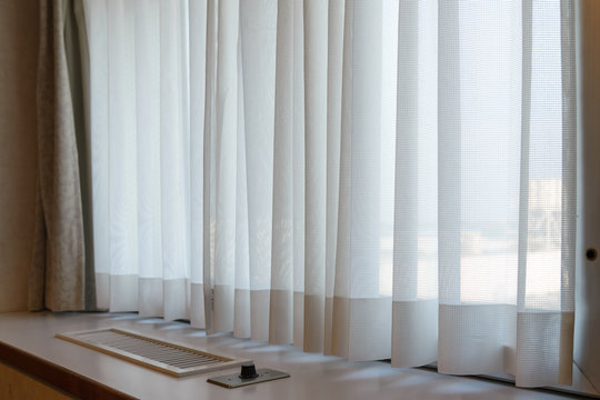 sunshire light looking pass Translucent white fabric curtains and window glass fame and view outdoor background
