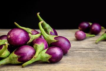 Fresh mini purple eggplant on wooden background