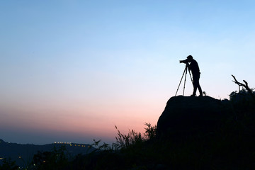 silhouette of photographer taking photo in the mountain and sunset .