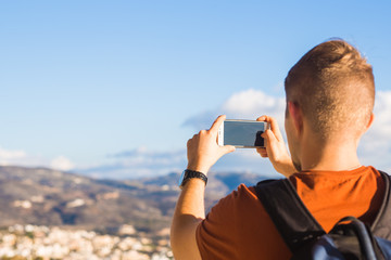 Travel, vacation, photographer and hitchhiker concept - raveler man photographed mountains and city in the smartphone
