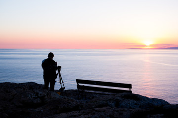 man photographer taking photos of sunset at the sea