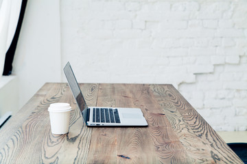 Workplace with notebook and cup of coffee on wooden table in big spacious room. Natural lighting. Mockup with text space.