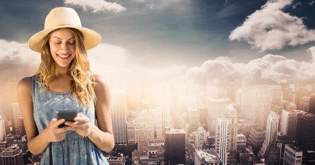 Woman in summer clothes texting against skyline with clouds