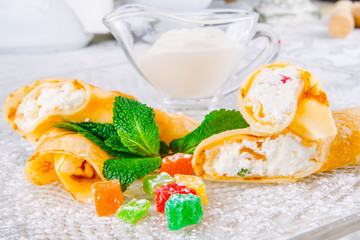 Rolled crepes with cottage cheese and candied fruits