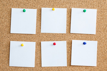 Six white memo reminder cards pinned to cork board. Blank empty copy space square papers background.