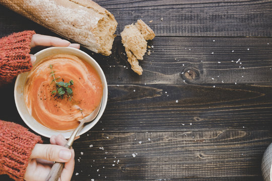 Hands holding hot cream soup on the wooden table, top view. With copy space