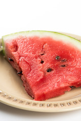 Triangle slice of watermelon on the plate isolated over white background