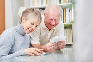 Senioren mit Kassenzetteln und Taschenrechner