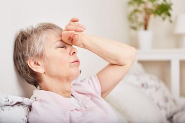 Seniorin mit Kopfschmerzen liegt im Bett