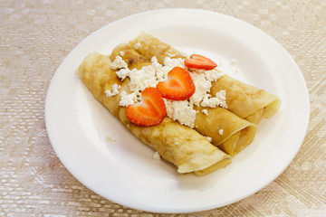 Dessert made from pancakes stuffed with cottage cheese and strawberries. horizontal