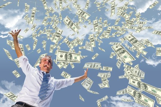 Excited business man with money rain against sky