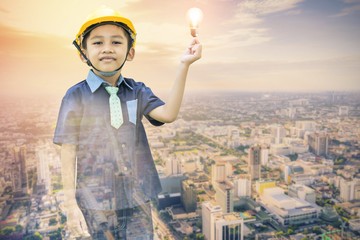 Double exposure of the Asian boy dressed as an engineer wearing a safety hat holding a light bulb on a cityscape backdrop-Imagination and creativity concepts.
