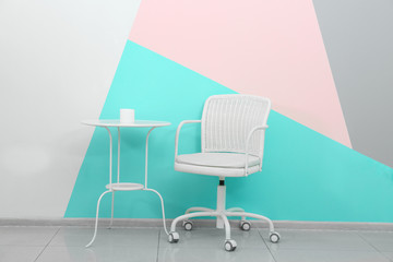 Trendy white furniture near wall with mint color