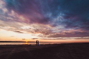 Wedding couple on a walk bride and groom sea field sunset architecture grass sand