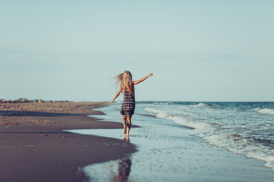 the Happy Woman running along the beach