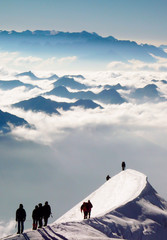 Foto op Aluminium Alpinisme group of male mountain climbers headed to the summit of a high alpine peak in the Swiss Alps along a very narrow and exposed snow and ice ridge