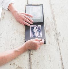 Fotoalbum mit schwarz-weiß Bildern in den Händen einer älteren Frau