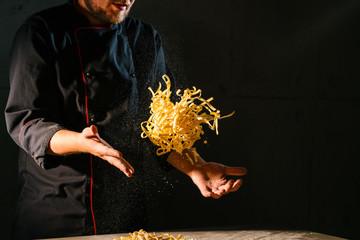Chef's hands toss and shake the ribbon-like Italian pasta over the wooden kitchen table before preparing the dish. Hard contrast light from the side.