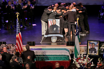 The family of New York City Police Department (NYPD) officer Miosotis Familia hug during her funeral in New York City