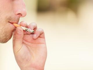 Adult man smoking cigarette outside