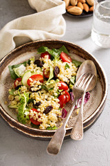 Warm salad with bulgur, vegetables and leaves