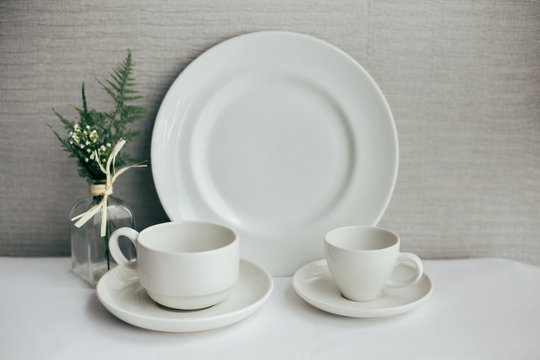 Set of beautiful exquisite dinnerware and cups made from white luxurious china and porcelain, set up for mockup on isolated background