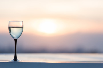 A glass with a white wine in the light of the setting sun. Vibrant alcohol background.
