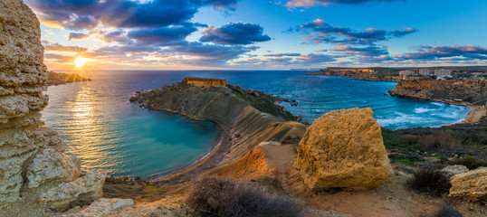 Mgarr, Malta - Panorama of Gnejna bay and Golden Bay, the two most beautiful beaches in Malta at sunset with beautiful colorful sky and golden rocks taken from Ta Lippija Wall mural