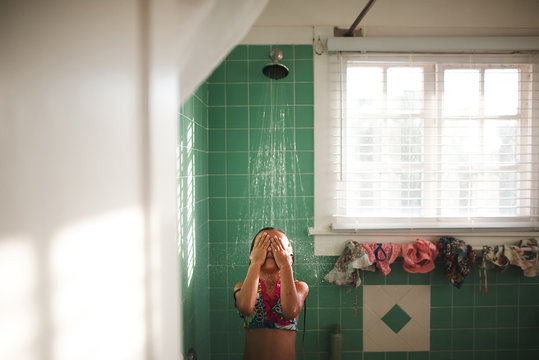 Young girl taking shower in bathing suit.