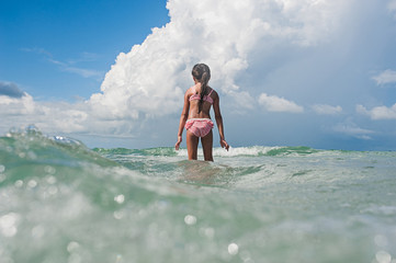 Rear view of girl walking in the water