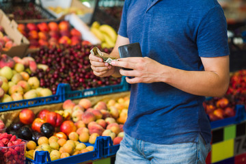Young man paying cash at food market. Cash payment in close-up. Fresh fruits in the background.