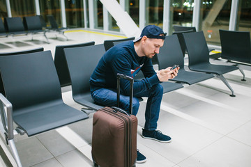 A young man with a suitcase sits in the airport waiting room and uses a mobile phone. Night flight, transfer, waiting at the airport.