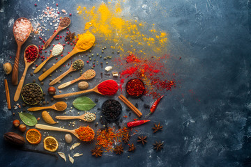 Various indian spices in wooden and silver spoons and metal bowls, seeds, herbs and nuts on dark stone table. Colorful spices, top view,  space for text. Organic food, healthy lifestyle.