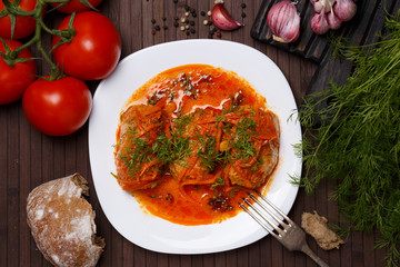 Cabbage rolls in tomato gravy with carrots and fresh dill on a white plate. Top view.