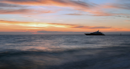 Luxury 'Super Yacht' moored up against a romantic vibrant sunset