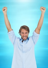 Man celebrating against blurry blue background