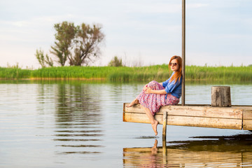 Beautiful young red woman sitting on a wooden pier in a colorful long sarafan dress and putting her leg in a water
