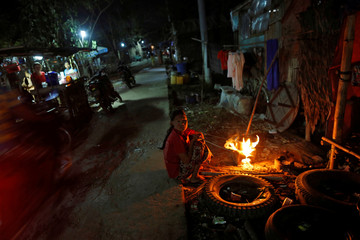 A woman cooks dinner for her family outside her house in Dala township, outside Yangon