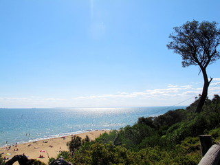 View of Sandringham beach at Melbourne, Australia. Have people walking, swimming and sunbathing round of coast.