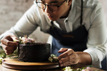Baker Man Decorating Chocolate Cake with Flowers