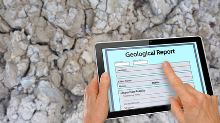 Hand completing online Geological Report on a computer tablet - infront of clay soil background