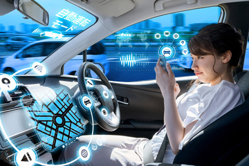 young woman using a smart phone in a autonomous car. driverless car. self driving vehicle. heads up display. automotive technology. right hand drive.