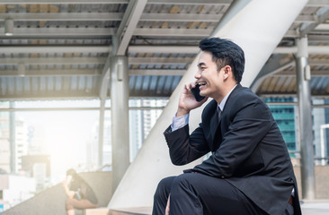 portrait of businessman talking on smartphone with building background in the downtown