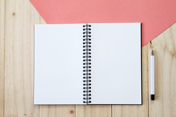 Still life, business, office supplies or education concept : Top view image of open notebook with blank pages and pen on wooden background, ready for adding or mock up