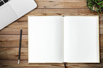 Top view of blank notebook, laptop and little tree page on wood background office desk with different objects. Minimal flat lay style