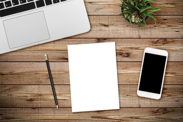 Top view of blank paper page, laptop and smartphone on wood background office desk with different objects. Minimal flat lay style