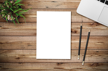 Modern workplace with notebook, blank paper, pencil and little tree copy space on wood background. Top view. Flat lay style. Wall mural