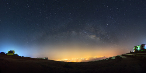 Panorama milky way galaxy and city light at Phutabberk Phetchabun in Thailand.Long exposure photograph.with grain