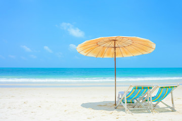 Blue sea and white sand beach with beach chairs and parasol